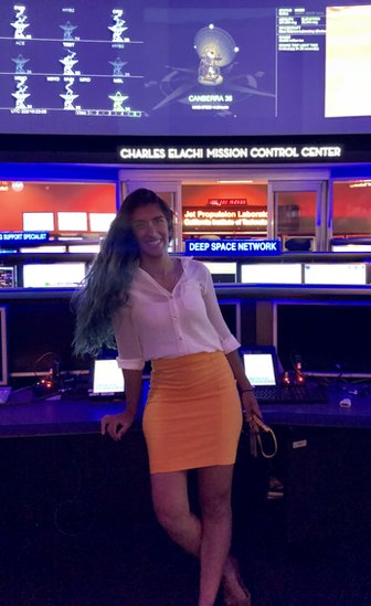A woman stands in front of signs saying 'Charles Elachi Mission Control Center' and 'Deep Space Network'. Above are screens with radio telescopes and the data they are receiving