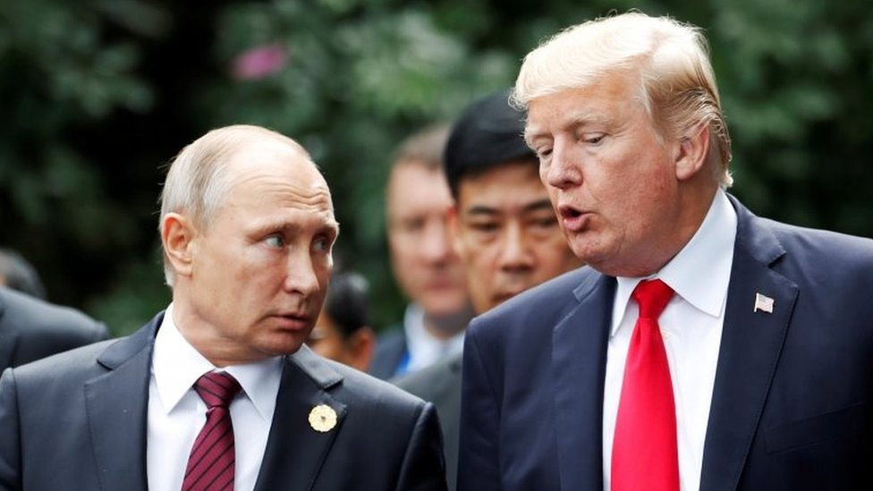 U.S. President Donald Trump and Russia's President Vladimir Putin talk during the family photo session at the APEC Summit in Danang, Vietnam 11 November 2017.