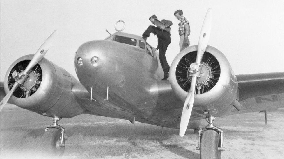 Нунан і Ерхарт оглядають свій літак Lockheed
