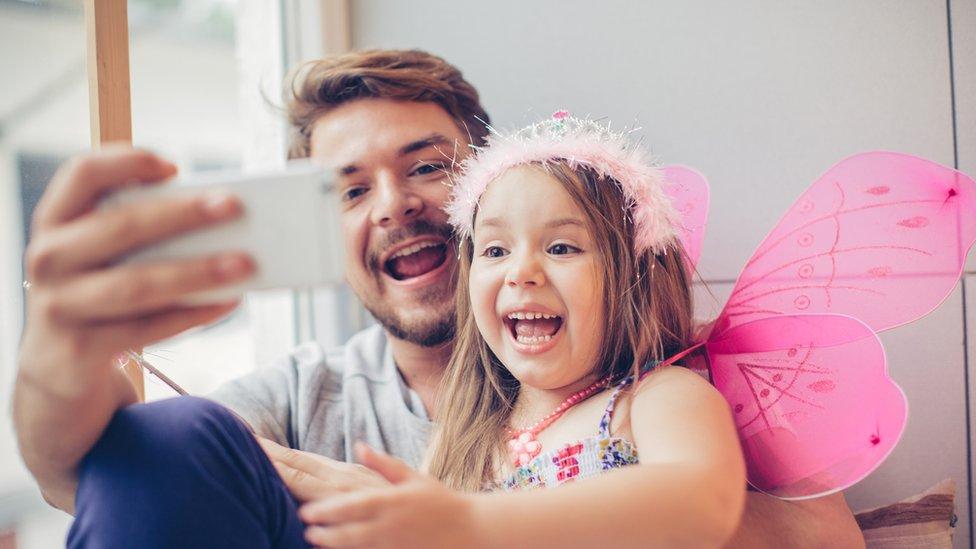 padre e hija usando celular