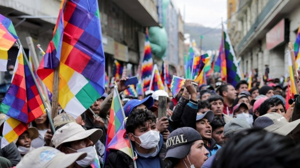 A crowd of protesters waved the multicoloured Wiphala flag