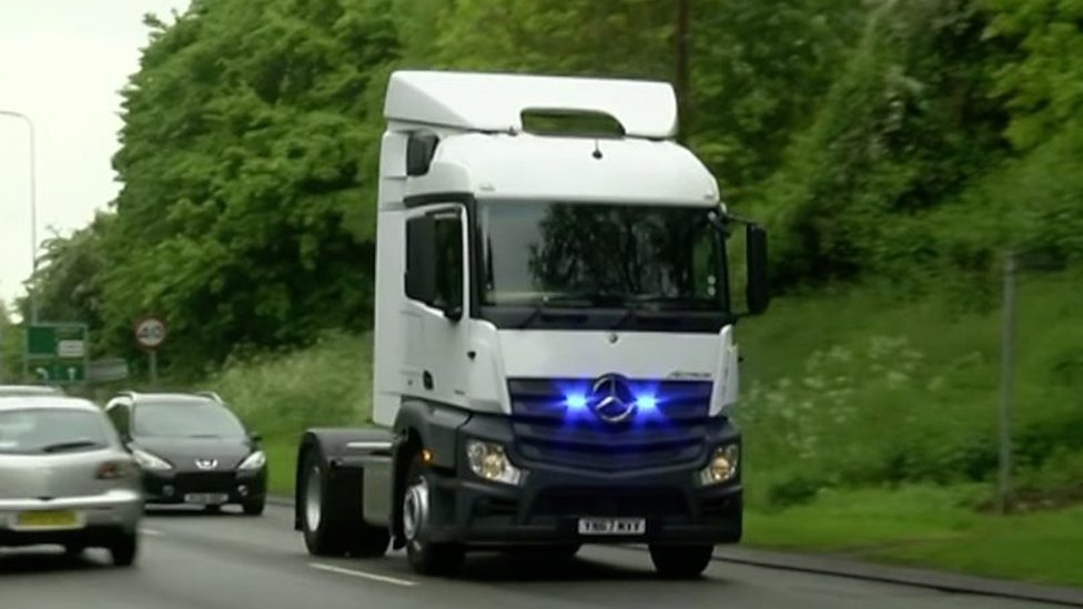 M40 Lorry driver makes card payment on phone at wheel