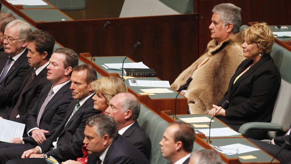 Ken Wyatt, wearing a traditional kangaroo skin coat, sits in parliament with other MPs