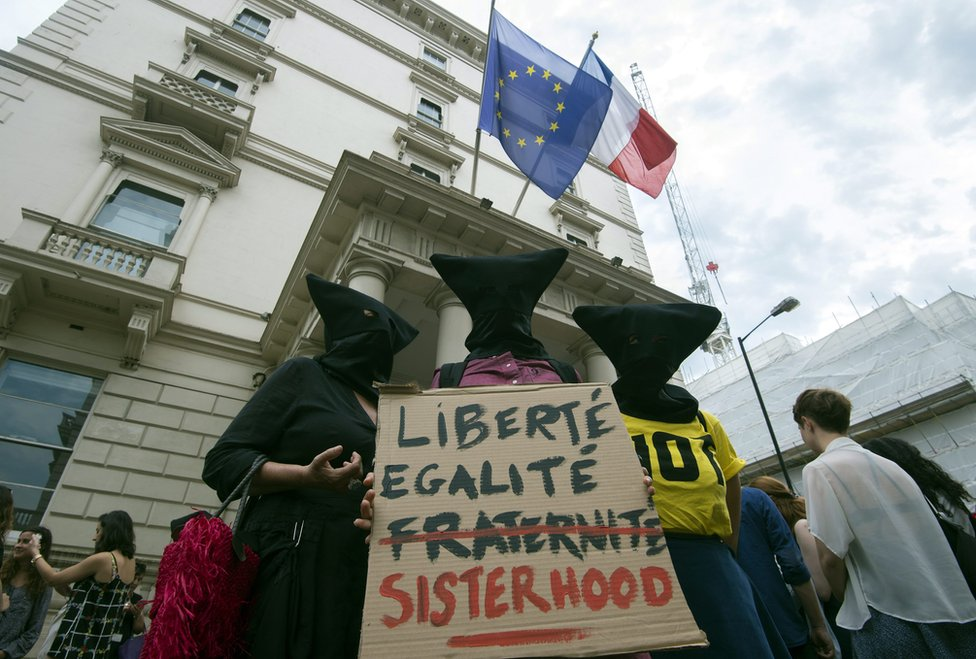 Women carrying sign reading liberte egalite fraternite but the fraternite is crossed out and replaced with sisterhood