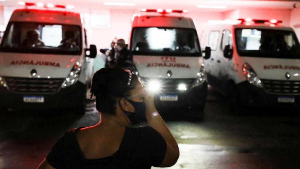 À noite e em frente a três ambulâncias estacionadas, mulher a aparece com a mão no rosto, gesto que remete a preocupação