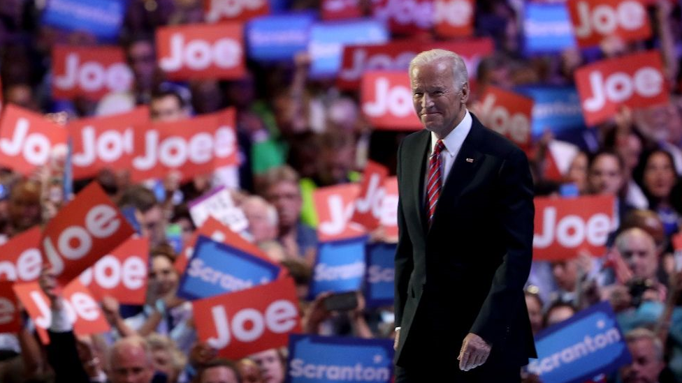 Joe Biden on stage in front of a crowd holding up signs with his name on them.