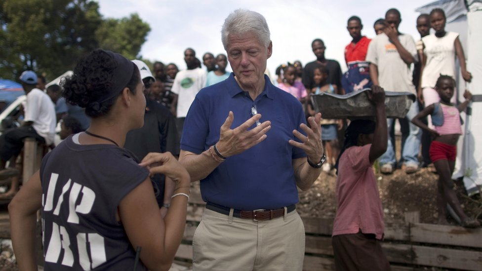 UN special envoy to Haiti, Bill Clinton (C) talks with an NGO worker in Port-au-Prince, Haiti, on 6 October 2010
