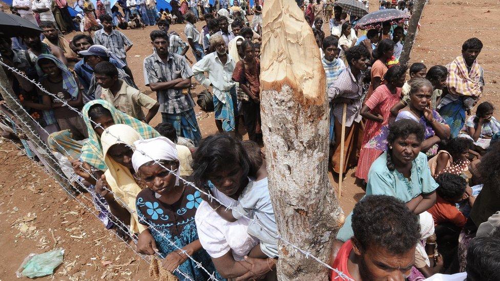 Internally displaced Sri Lankan people look on during a visit by United Nations Secretary-General Ban Ki-moon at Menik Farm refugee camp in Cheddikulam on May 23, 2009