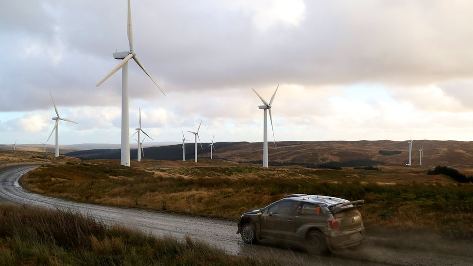A car drives in front of wind turbines in Newtown, Powys