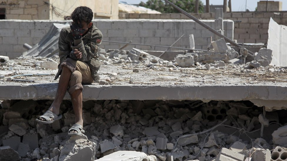 A Syrian man sits amid the rubble of a building destroyed in a reported government air strike in Saraqeb, Idlib province (7 May 2019)