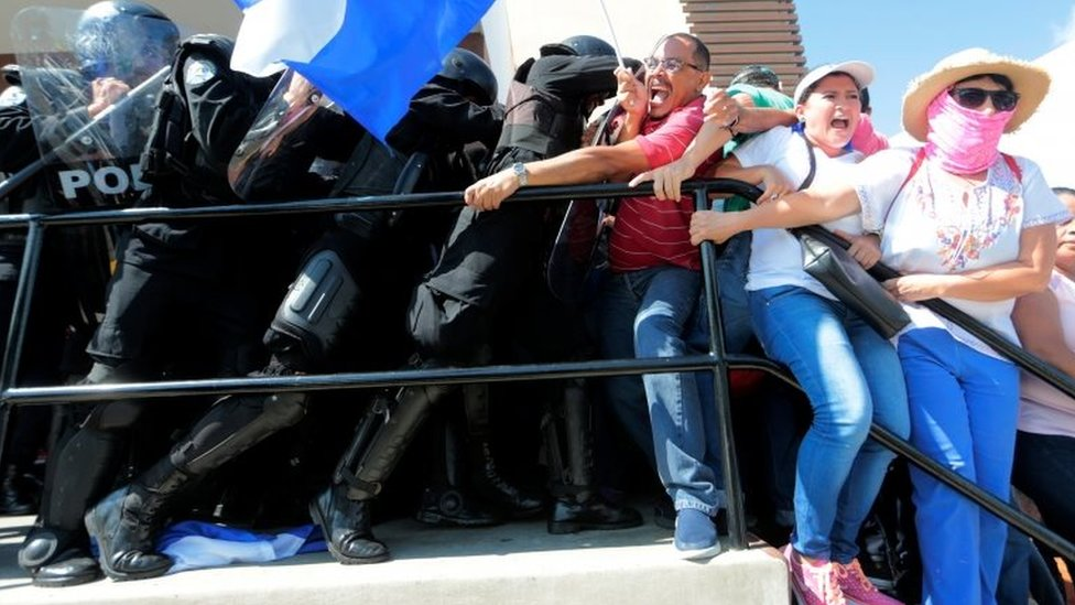Riot police try to detain protesters during a march against Nicaraguan President Daniel Ortega in Managua