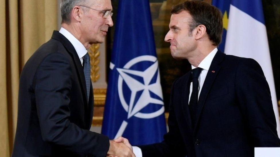 الرئيس الفرنسي ماكرون يصافح أمين عام حلف الناتو ينس ستولتينبيرج