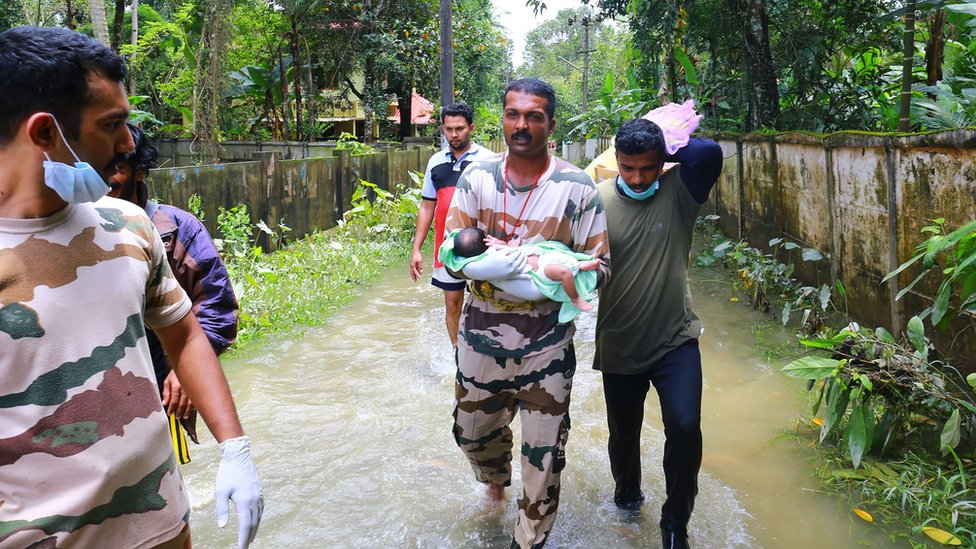 A worker carries a baby boy rescued with his family in Chengannur following widespread flooding in the south Indian state of Kerala on August 20, 2018