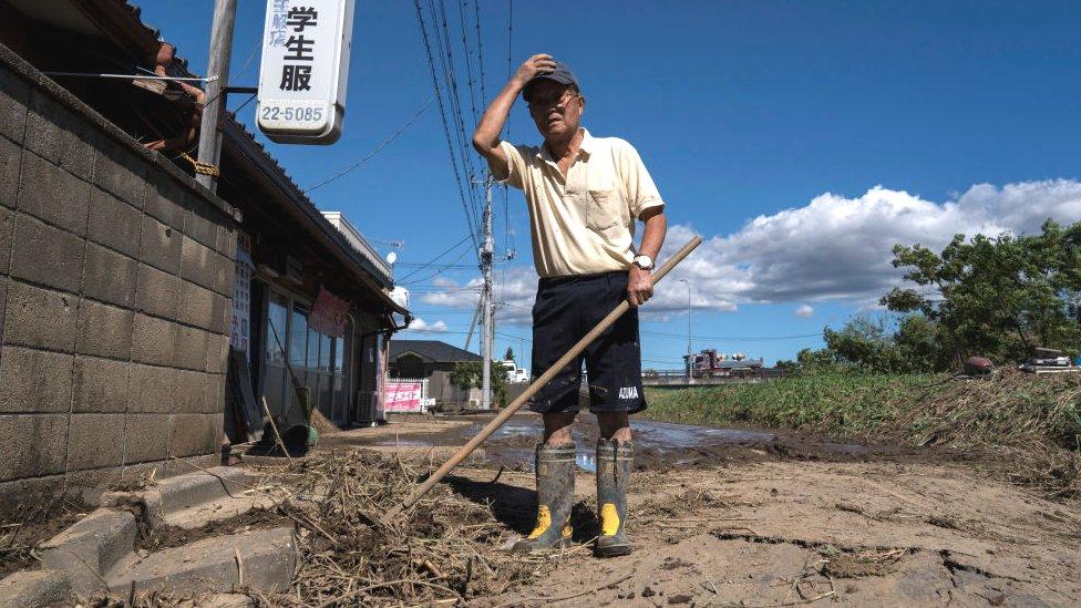 رجل ينظف آثار الإعصار