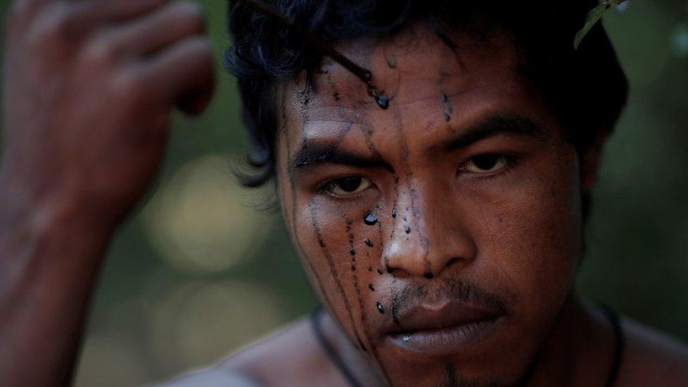 Paulo Paulino Guajajara applies face paint in September
