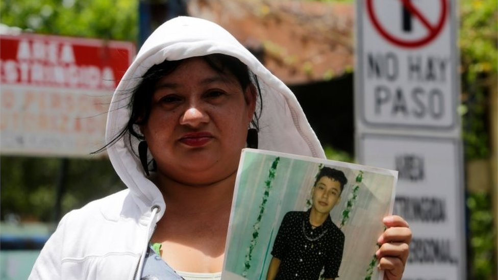 """A relative of an imprisoned protester holds his portrait outside """"El Chipote"""" prison in Managua, while demanding his release on July 18, 2018."""