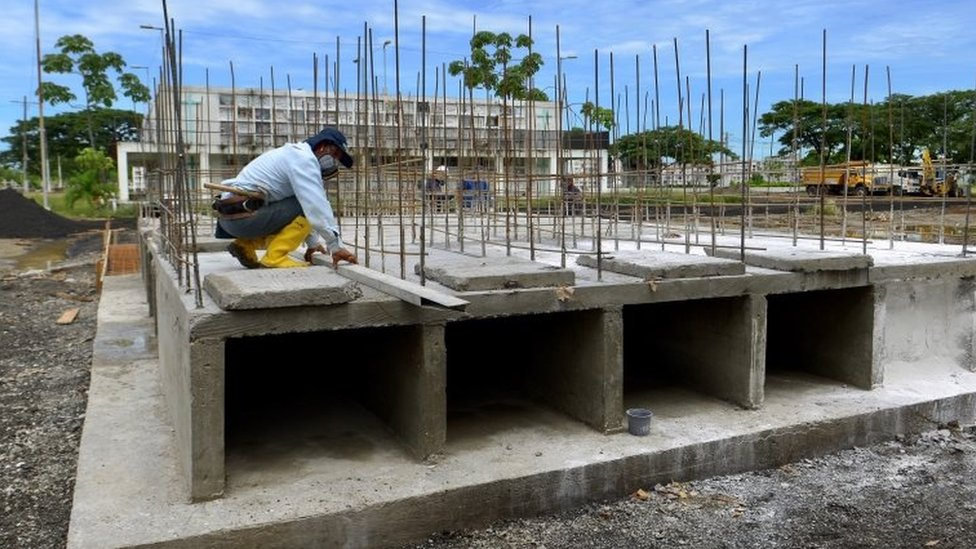 A construction worker, building extra niches in a cemetery