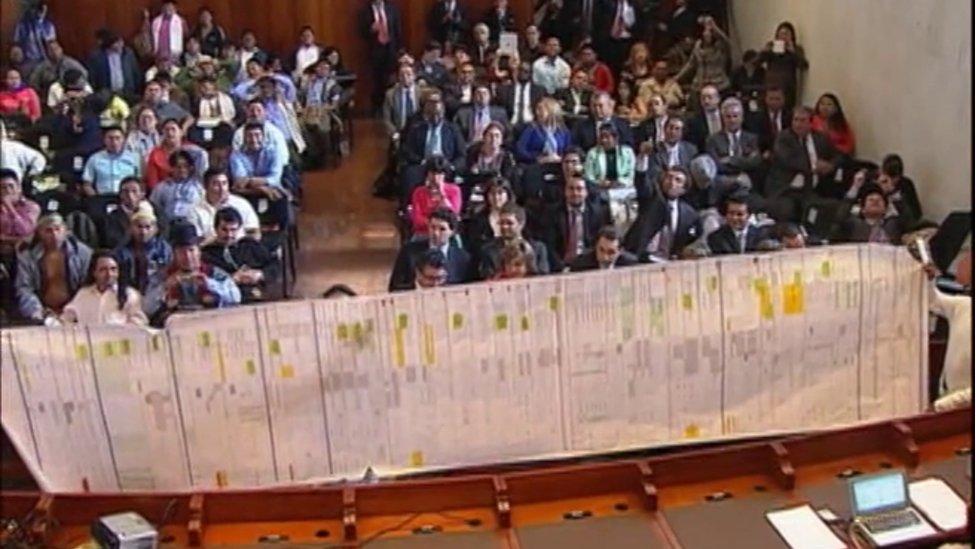 Presentan un documento ante una sala llena de personas