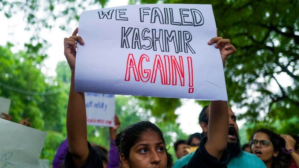 An Indian activist holds a placard during a demonstration to protest against the presidential decree abolishing Article 370