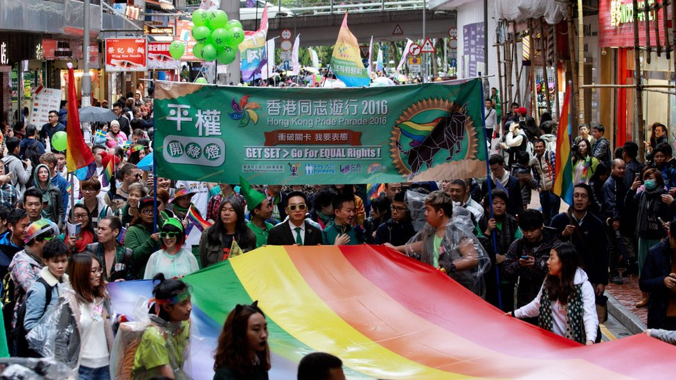Participants of Hong Kong's annual pride parade walk through the streets with a large rainbow flag on November 26, 2016