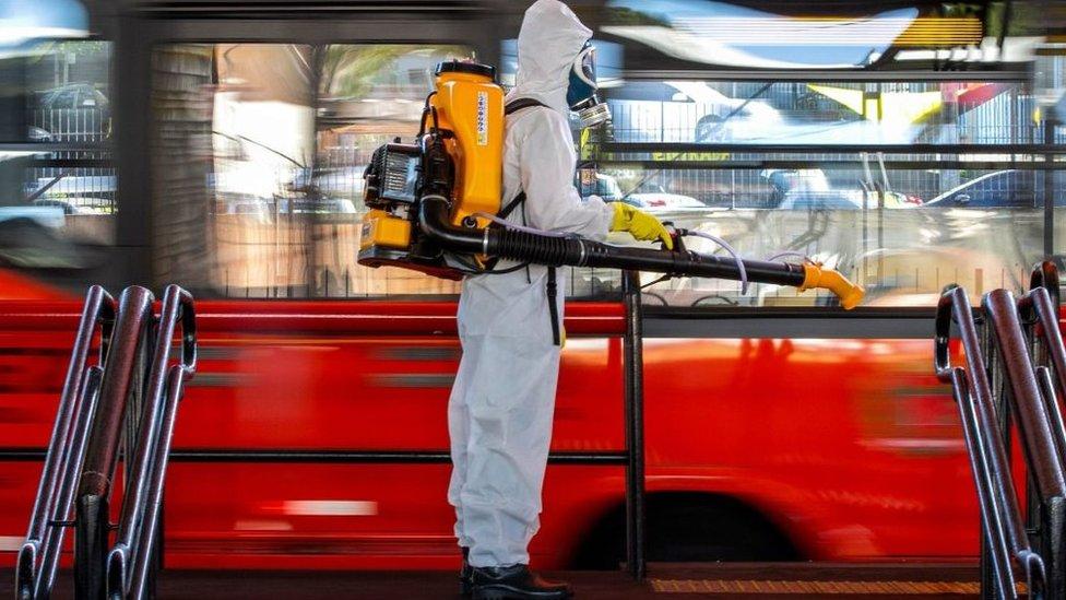 Profissional desinfecta ponto de ônibus em Curitiba