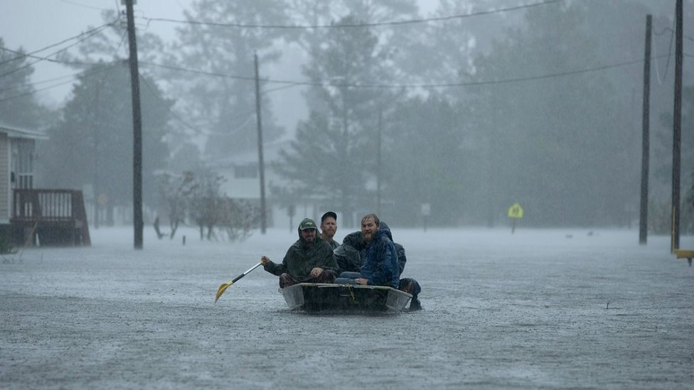 Volunteers in a small boat in flooded conditions