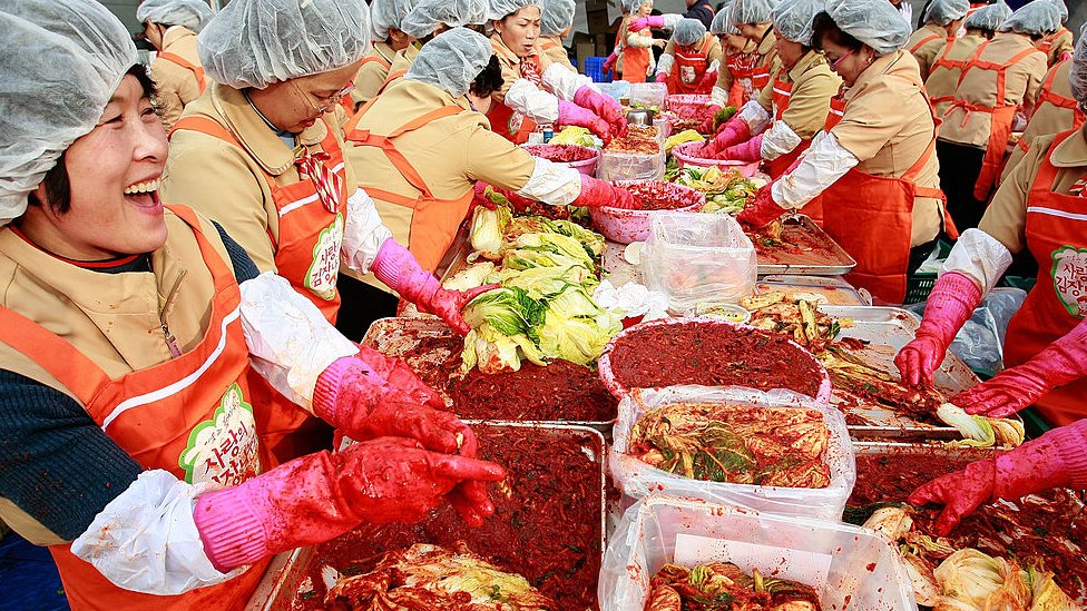 Korean women make kimchi for donation to the poor in Seoul