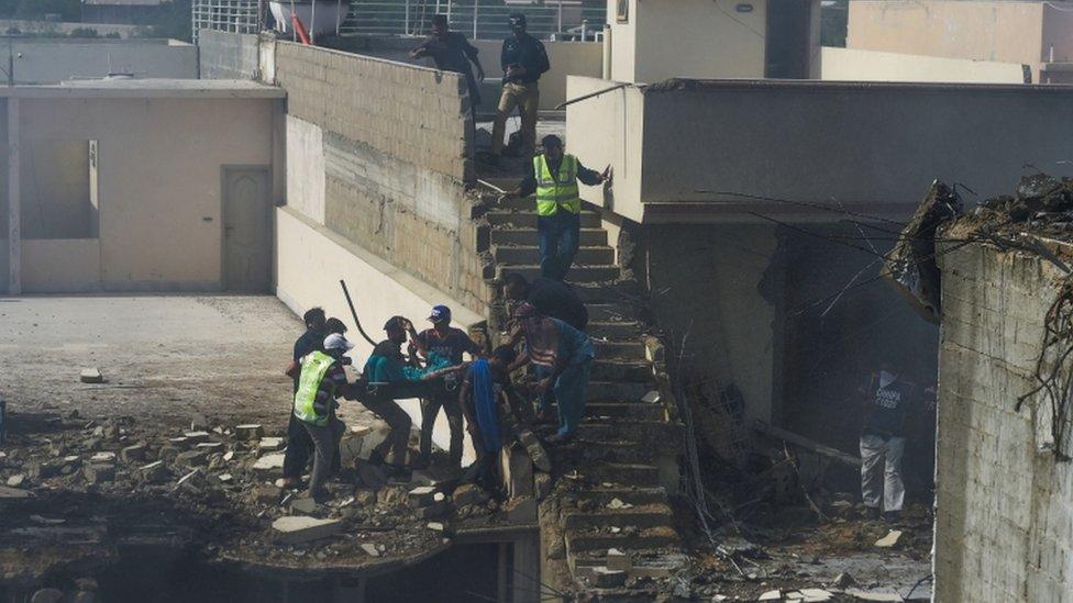 Los equipos de rescate evacúan a un residente herido de la zona, donde varias viviendas fueron destruidas.
