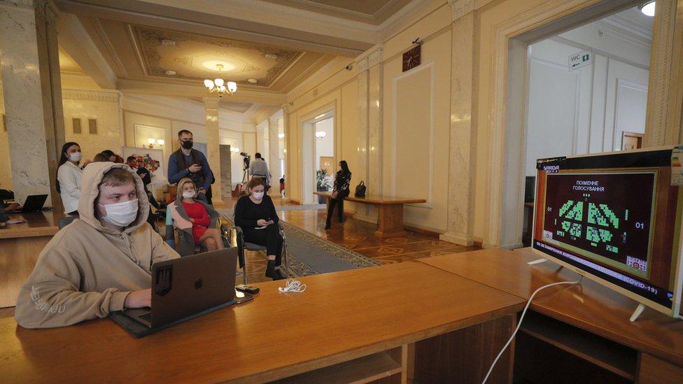 Un grupo de personas con mascarillas miran la pantalla de una computadora