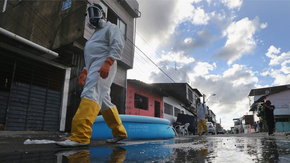 Health workers walk while fumigating in an attempt to eradicate the mosquito which transmits the Zika virus in Recife, Pernambuco state, Brazil in 2016