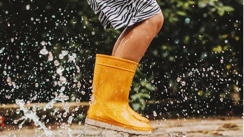 Niño con botas de agua saltando sobre la lluvia.