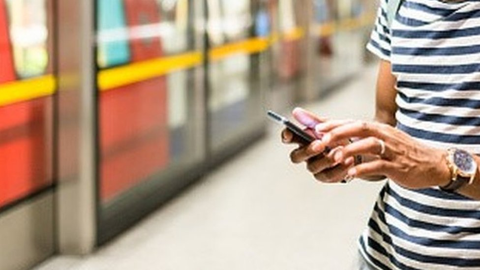 Mobile phone being used on Tube