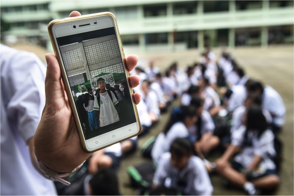 A Thai student shows a picture of missing classmate Prachak Sutham