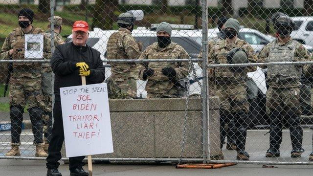 Soldados de la Guardia NAcional y un crítico de Biden