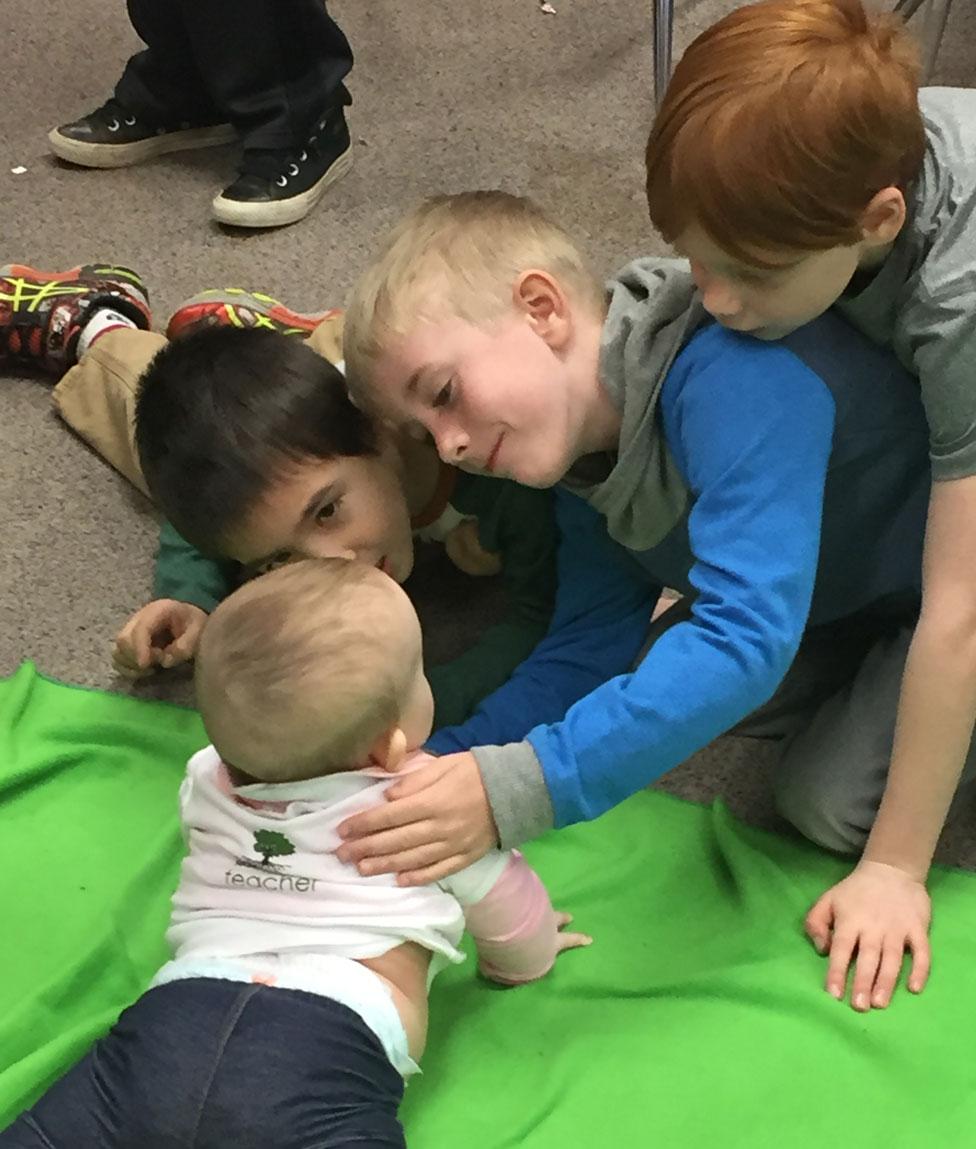 Un grupo de varones con un bebé durante un programa de Roots of Empathy.