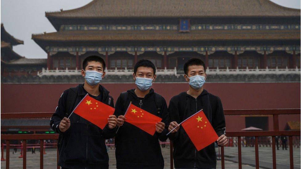 Jóvenes con mascarillas y banderas de China