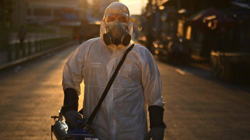 Trabajador desinfectando una calle en San Salvador.