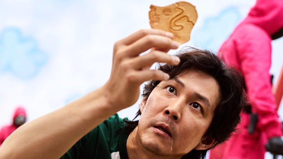 """Seong Gi-hun, uno de los personajes principales de """"El juego del calamar"""", sostiene una dalgona."""