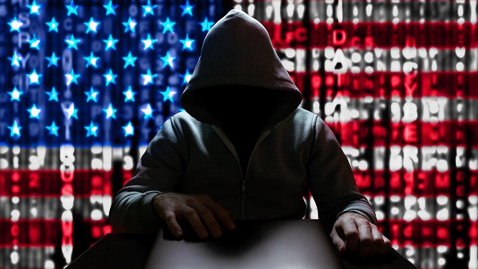 Un hacker con la bandera de EE.UU. de fondo