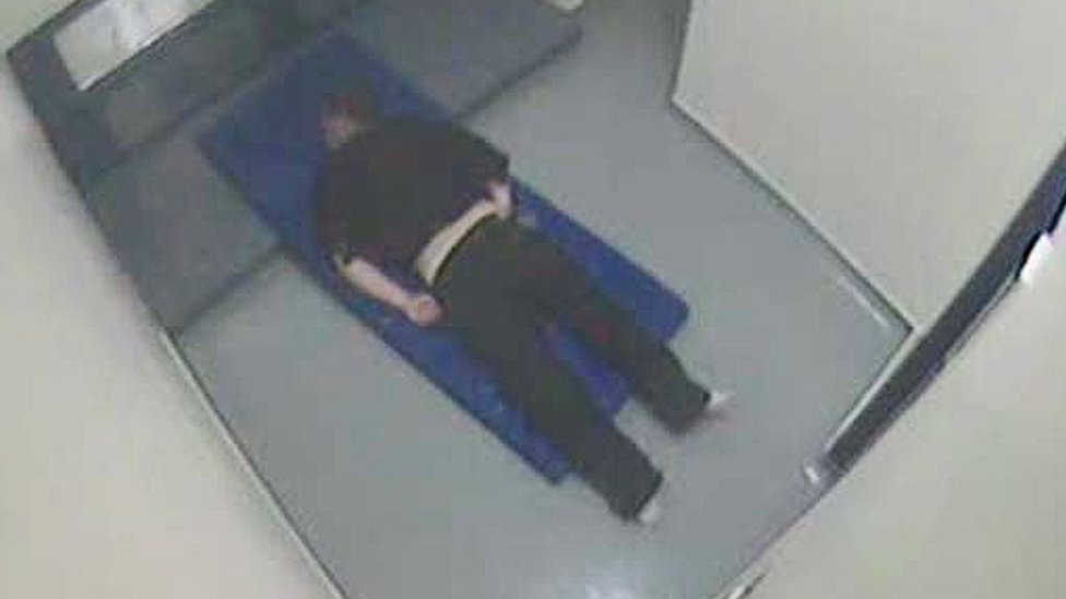 Thomas Orchard handcuffed and lying face down on a mattress in his cell