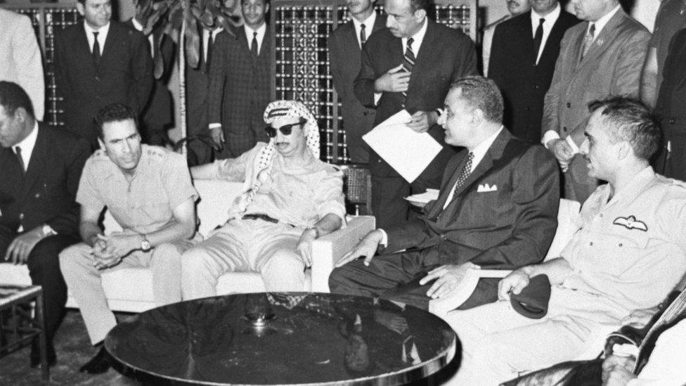 चश्मा लगाए यासिर अराफ़ात, बाईं तरफ कर्नल गद्दाफी और दाईं तरफ जमाल अब्दुल नासिर