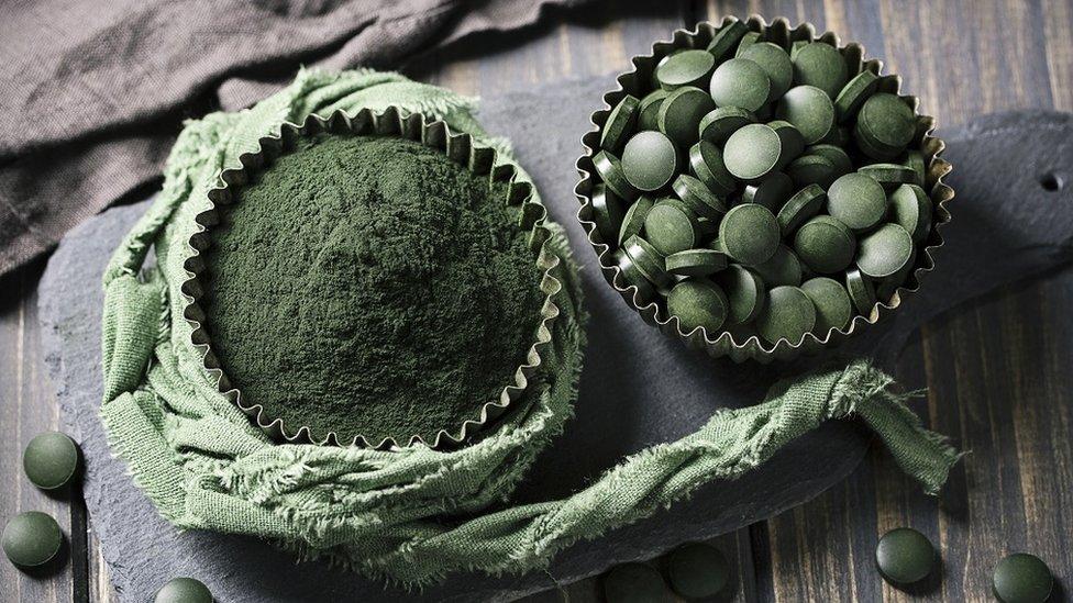 Spirulina tablets and powder in bowls