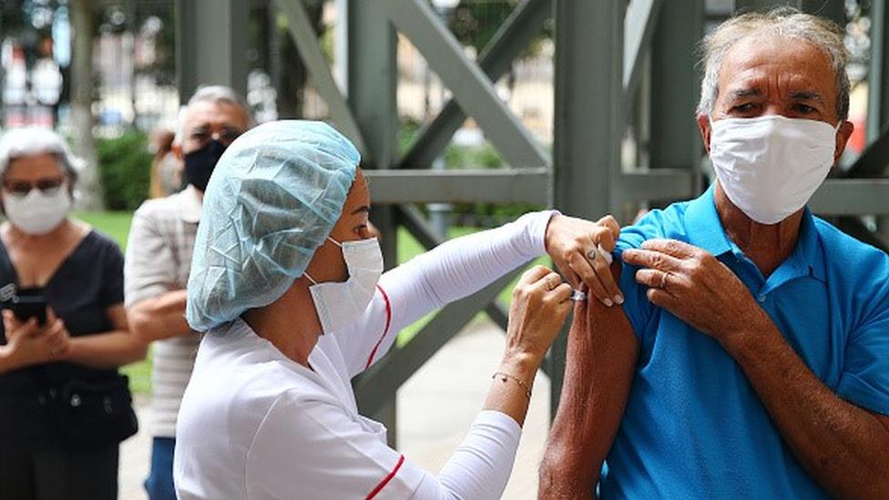 Enfermeira aplicando vacina no braço de homem