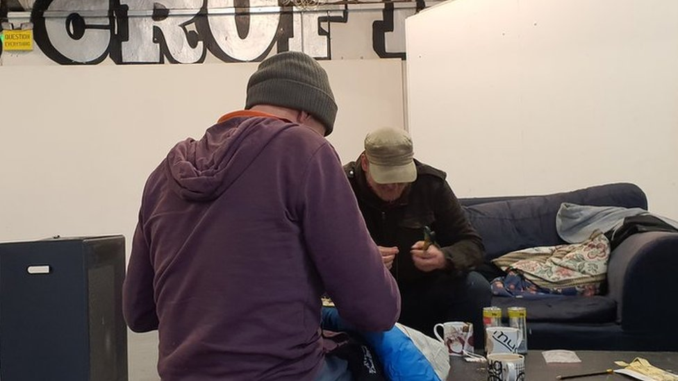 Two men sewing labels onto blankets for homeless people