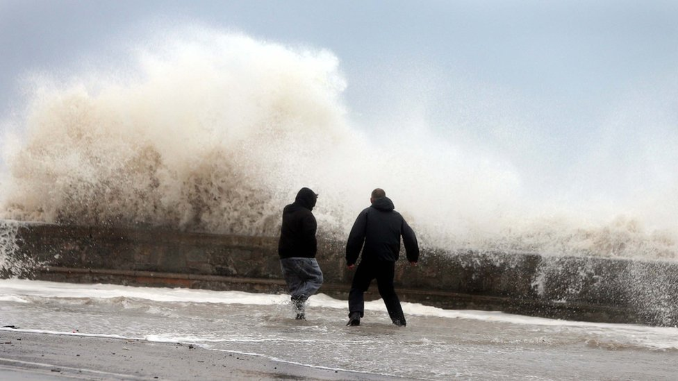 Two men standing on a sea wall as a wave breaks