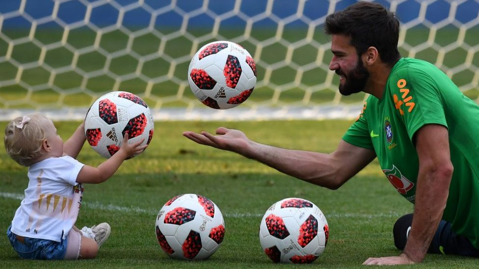 Footballer Alisson plays with daughter Julia