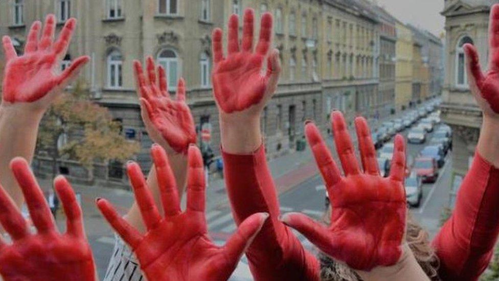 Manos de mujeres pintadas de rojo.