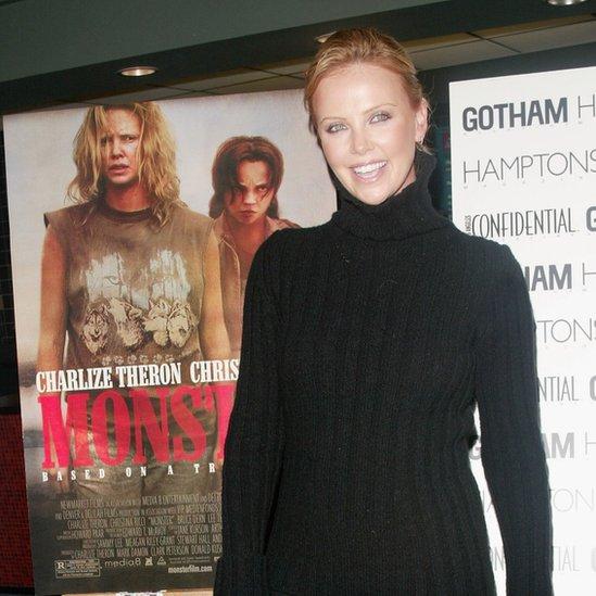 "Chralize Theron frente al afiche de la película ""Monster: asesina en serie"""