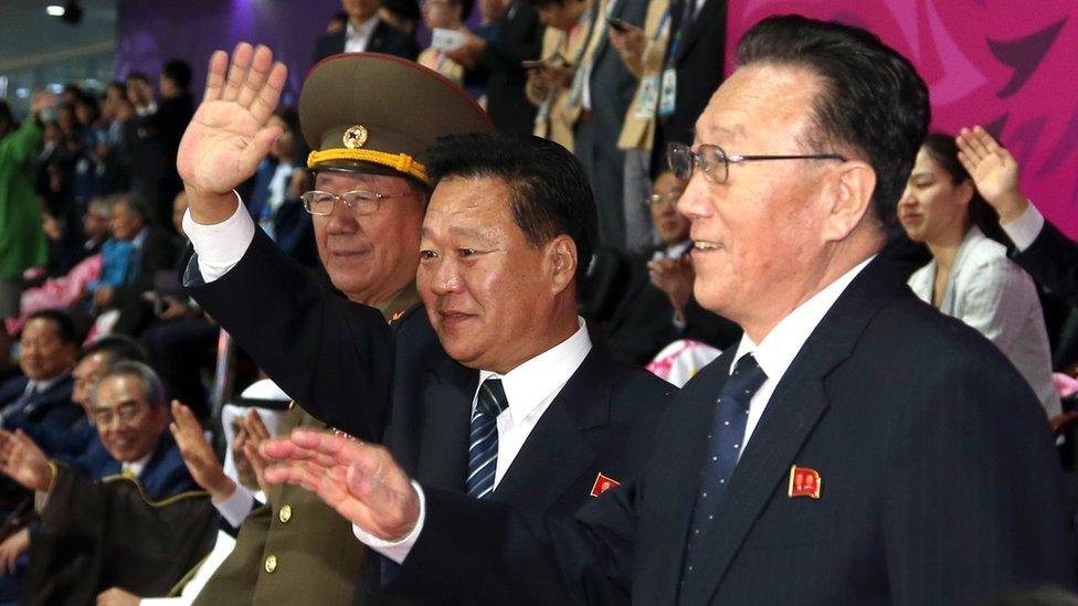 Hwang Pyong-so (L), Choe Ryong-hae (C) and Kim Yang-gon waving hands at Asian Games in Incheon in 2014