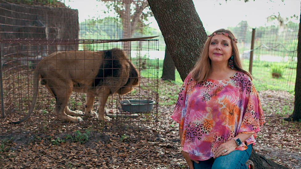 Carole Baskin and a lion in a cage